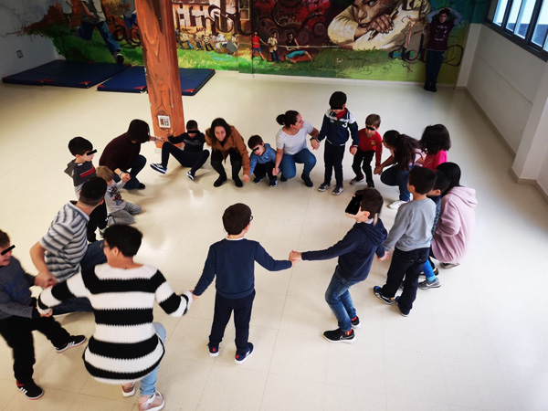 Children and adults playing a game in a circle at MIRAME