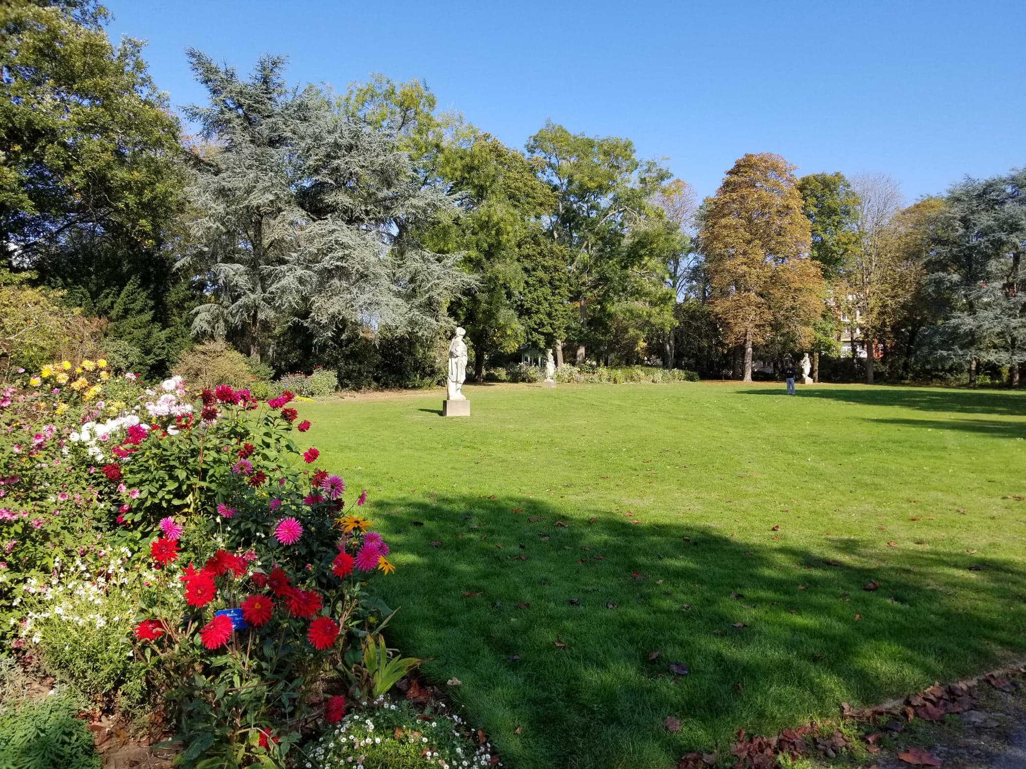 There are statues in the back, and on the left are some dahlia plants. At the right is a large grassy expanse
