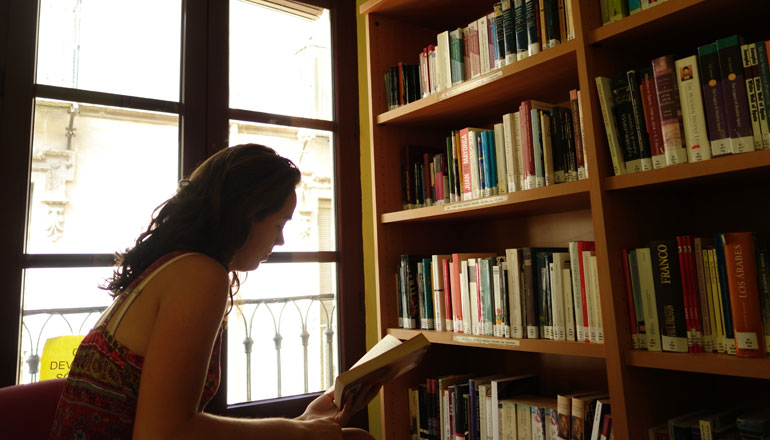 student reading in library in front of a window