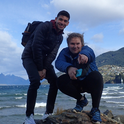 two students posing on rock with mountains and ocean in background