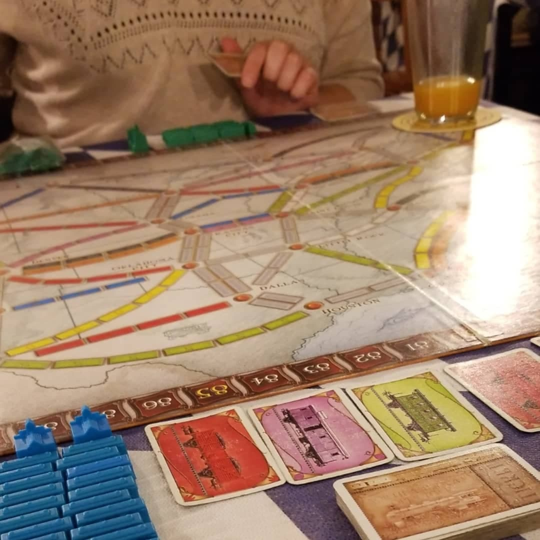 Detail shot of game including piles of cards, game board, blue rail tracks