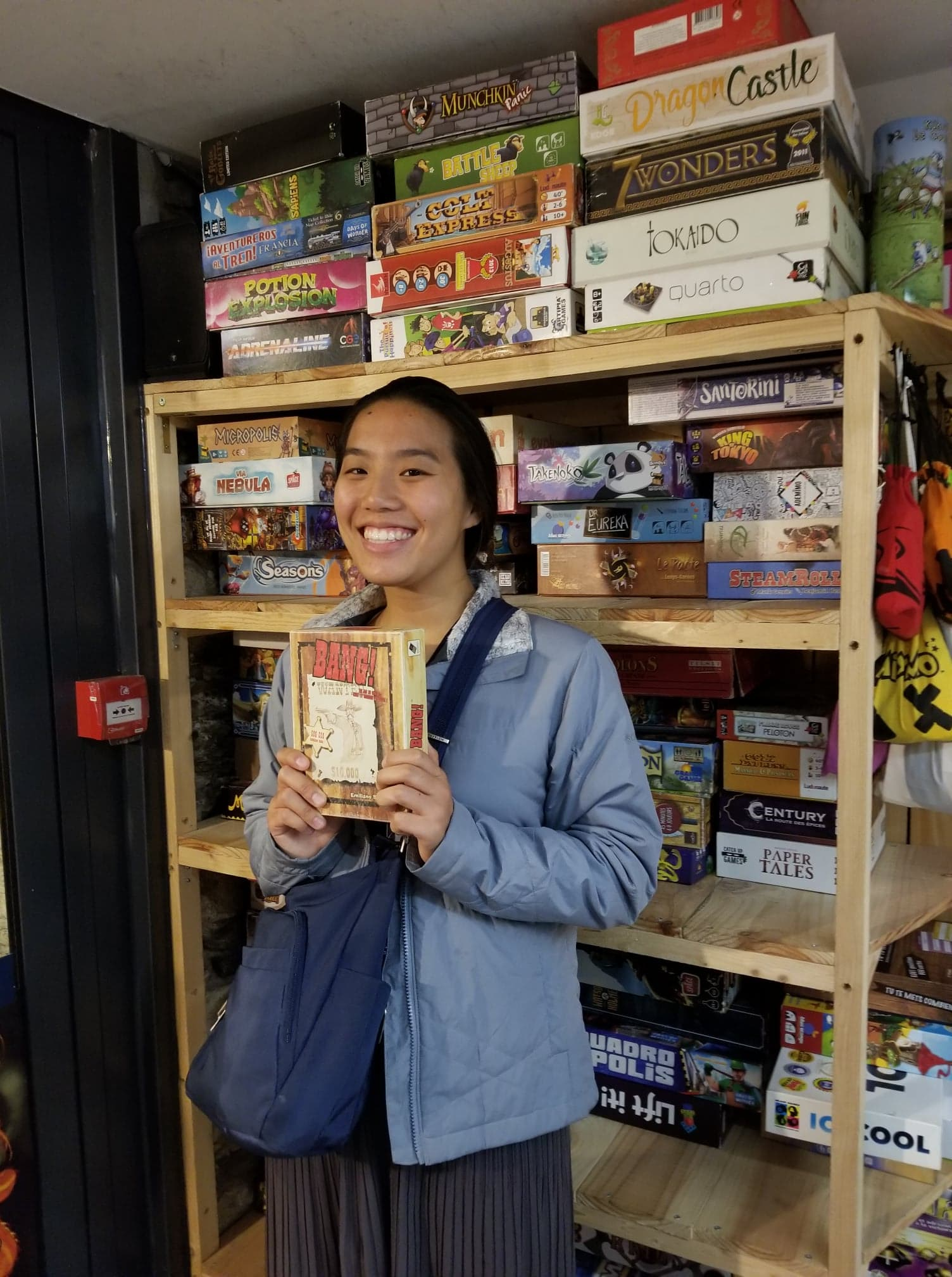 """Brittany in front of a bookshelf filled with games. In her hand she holds a box of the game named """"Bang!"""""""