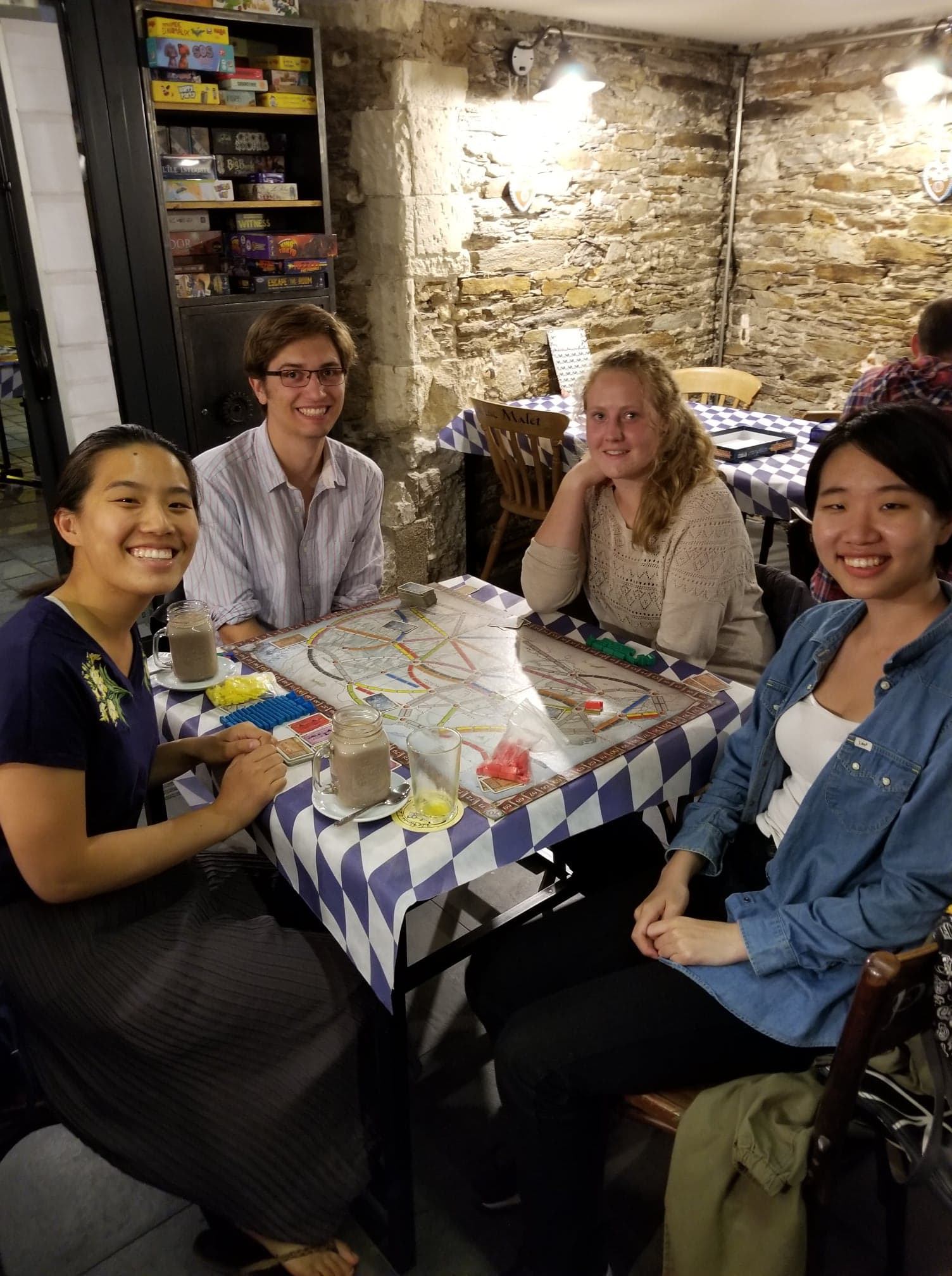 A group of four people seated by a table with Ticket to Ride on it