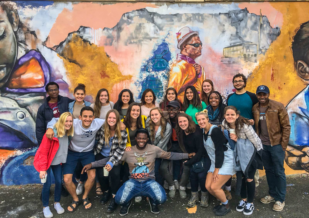 IES Abroad students and tutor guide in front of painted wall