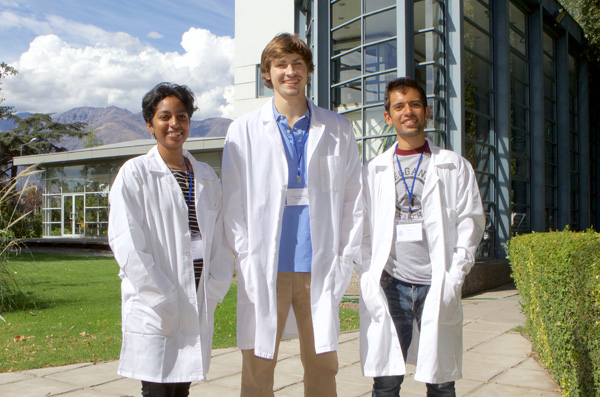 three interns abroad in lab coats standing and smiling outside of a building