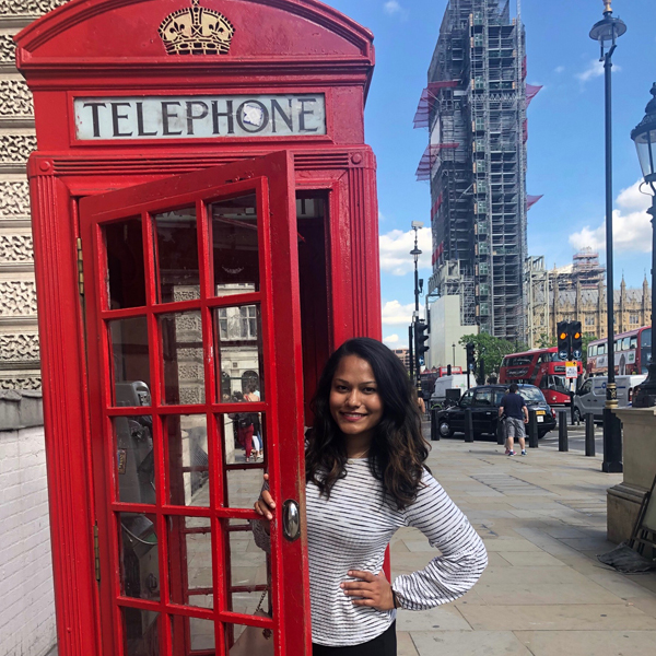 London intern partially in doorway of red telephone booth