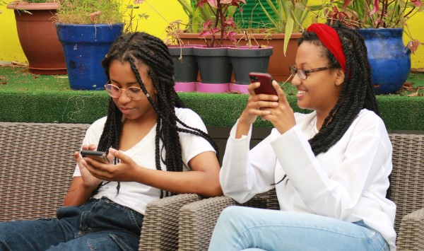 two students on their cell phones smiling