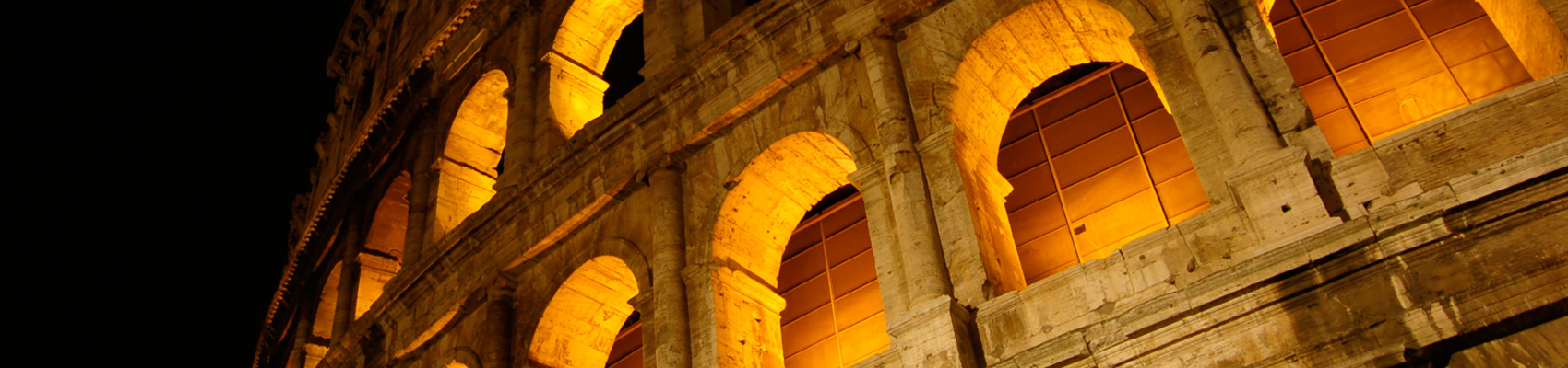 colosseum lit up at night under gold lights