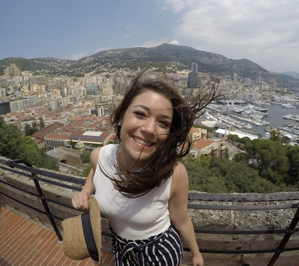 smiling student with wind-swept hair in front of mountain and city view