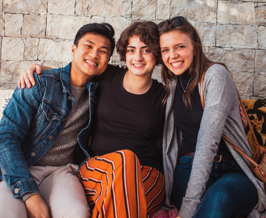 three students smiling sitting together against a stone wall
