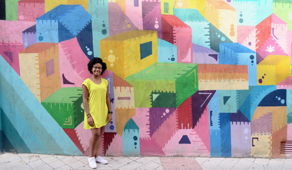 student in yellow dress leaning on a colorful mural