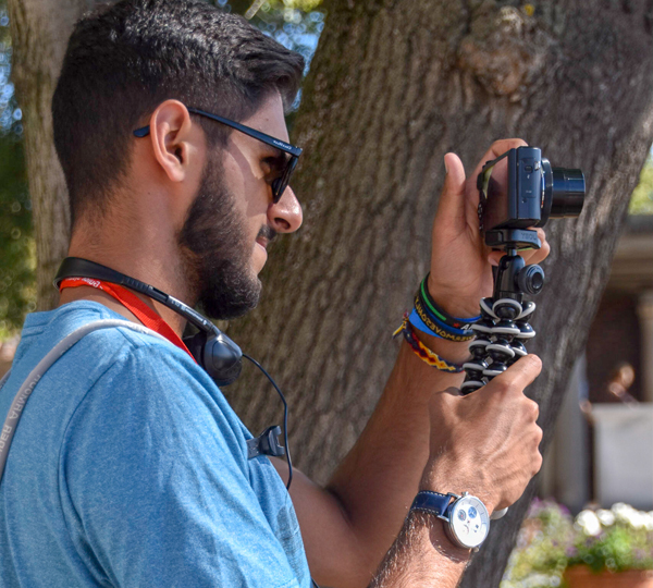 student wearing sunglasses and blue shirt holding camera with stabilizer