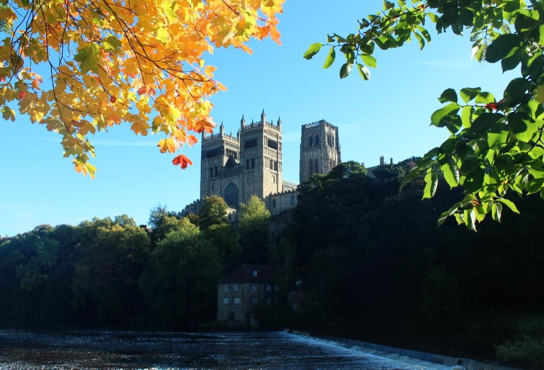 Photo of Durham Cathedral by the river, surrounded by fall leaves. Photo taken by Veronica Benduski, 2015