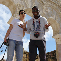 two students posing under arch in Granada, Spain. Student on right holding up hands in a shrug. Student on left flashing a peace sign