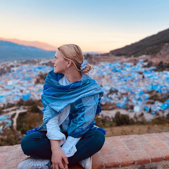 Blonde woman in blue scarf looking over her shoulder with hills and blue and white houses in the distance in Chefchaouen, Morocco