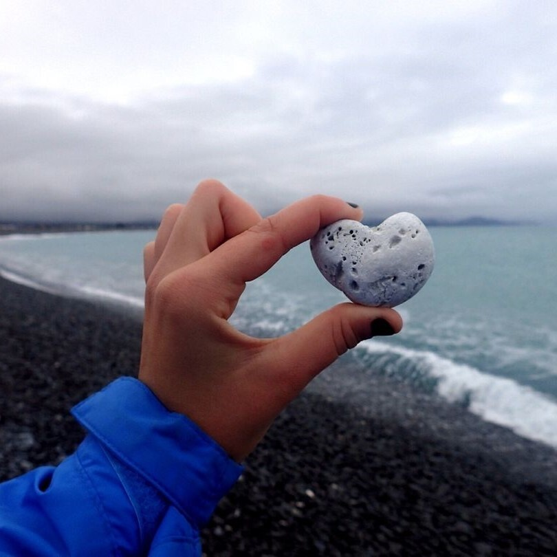 a hand holding a heart-shaped rock in front of the ocean