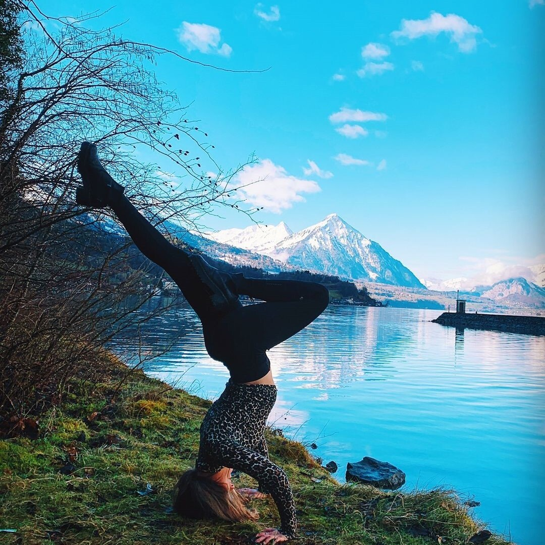 a student in a yoga headstand in front of a lake and mountain
