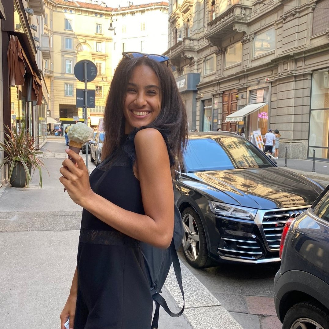 Woman in Italy smiling at the camera and holding an iced coffee
