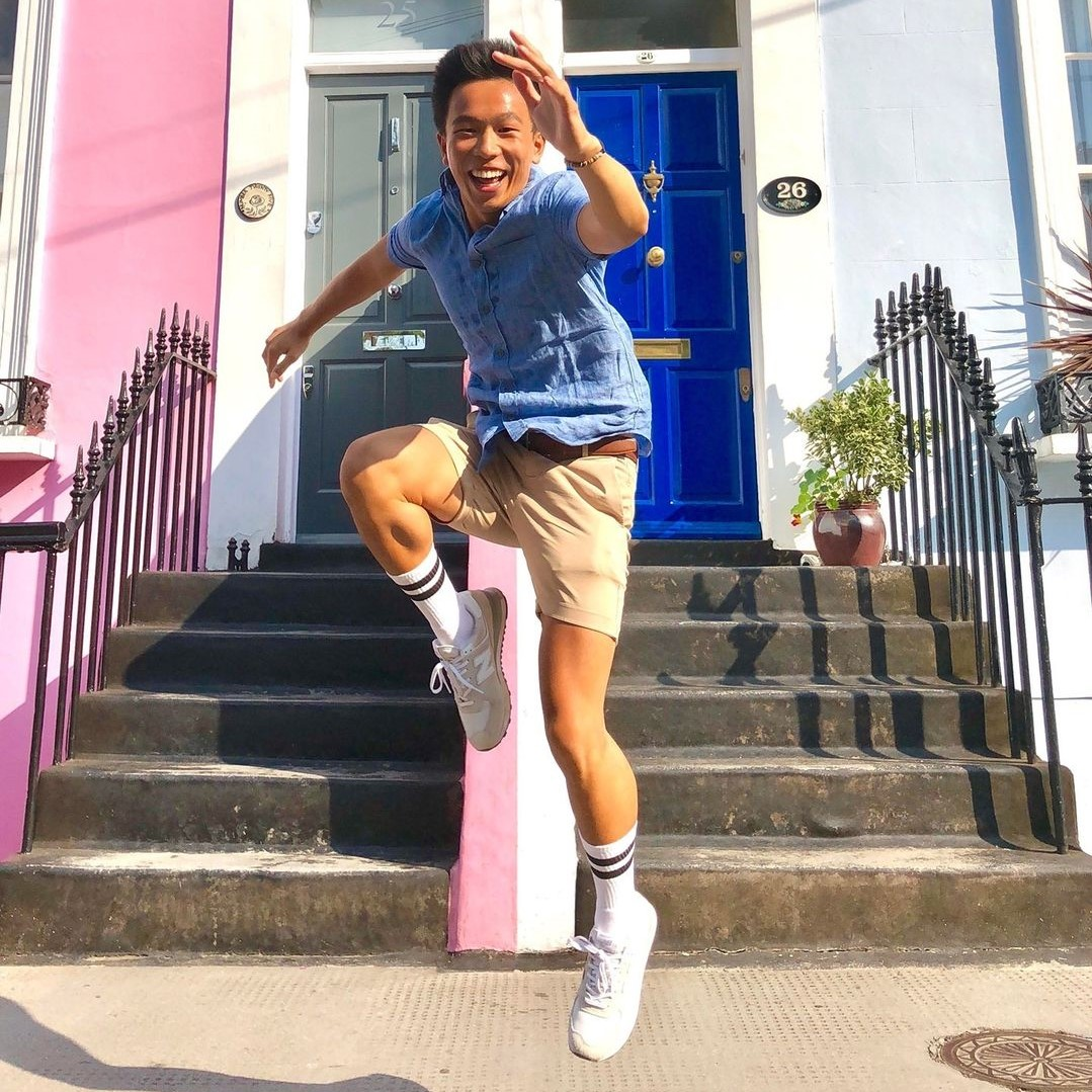 Young Man in London Jumping in front of Colorful Doors