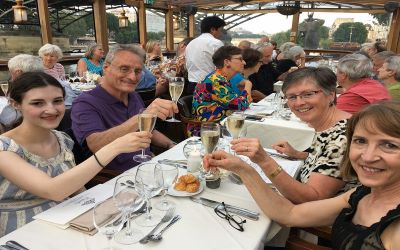 A group of alumni raising their glasses to cheers a lovely sunset dinner cruise on the Seine during an Alumni Weekend