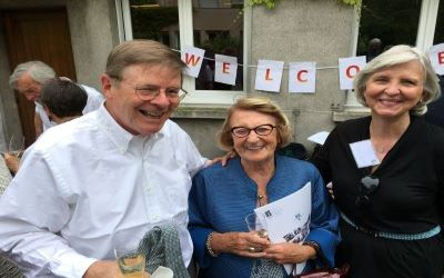 An alumnus and two alumna holding champagne glasses and laughing while at a reception at an Alumni Weekend in Paris