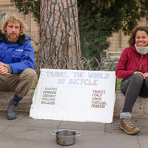 """Two people sitting on a curb with a sign that says """"travel the world by bicycle"""""""