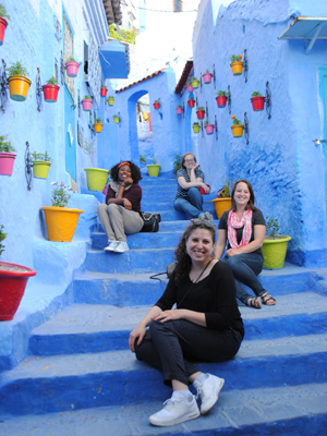 4 study abroad students sitting on blue steps staggered in Chefchouen Morocco