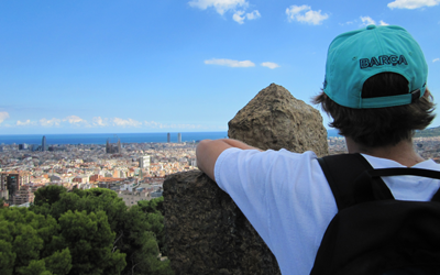 Male student in blue hat and white t-shirt with black backpack overlooking Barcelona