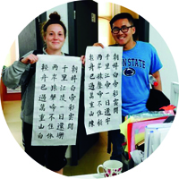 two students holding large papers with chinese calligraphy writing