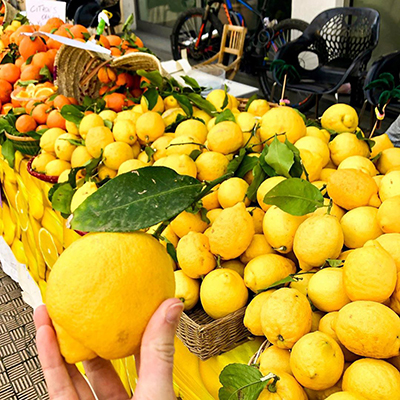 hand holding a yellow lemon at a farmers market