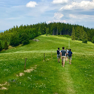 group of students walking in rolling, green hills