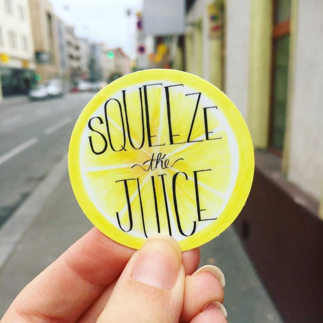 a hand holding up a circular sticker that looks like a lemon and it says squeeze the juice