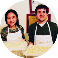 two students in kitchen aprons holding trays of fresh pasta