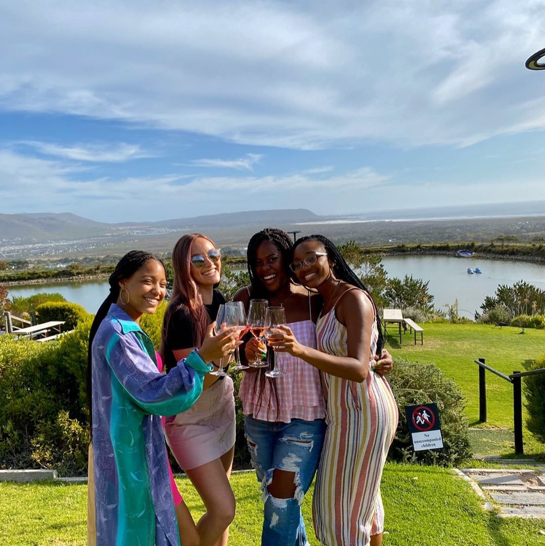 Four friends toasting at a vineyard in Cape Town