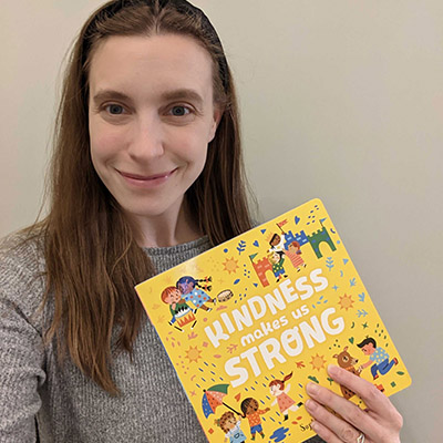 Abby posing with the children's book, Kindness is Strong.