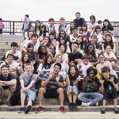 students in Japan with their language partners sitting on a staircase