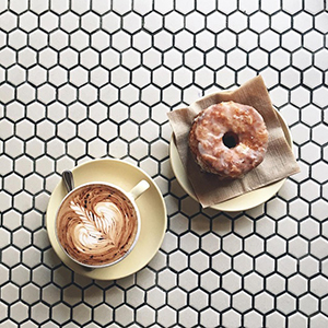 Aerial view of latte and bagel against white hexagonal tile