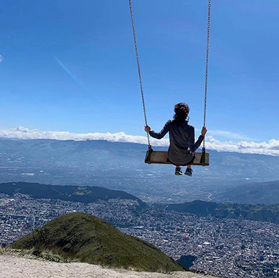 Student on a swing above the city scape in Ecuador