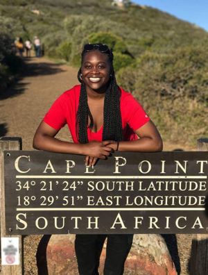 Student leaning on Cape Point sign