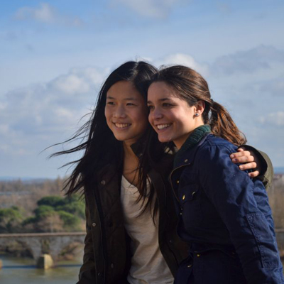 Two female study abroad students posing above a river in Spain