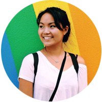 A smiling woman in front of a brightly colored wall