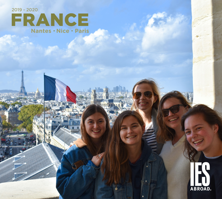 five students smiling with the eiffel tower and a france flag in the background