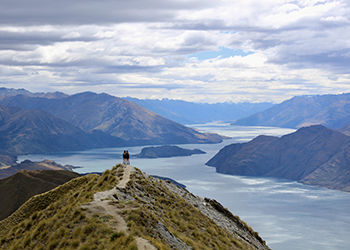 Person standing on a mountain overlooking water in New Zealand