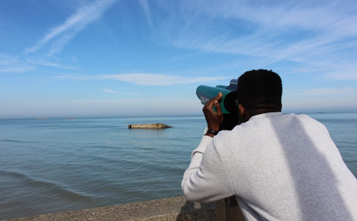 student looking through binoculars at the ocean