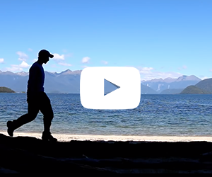 Student walking along alone near water and mountains in New Zealand