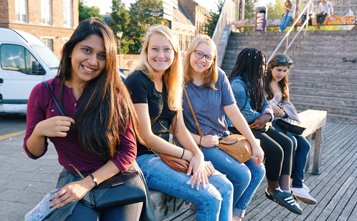 Female students sitting on a bench smiling at camera