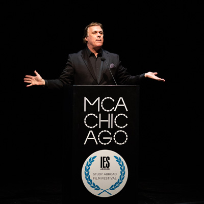 Richard Roeper standing behind a podium with MCA and IES Abroad Film Festival logos on it