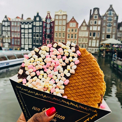 photographer holding a stroopwafel in front of the camera with buildings in the background