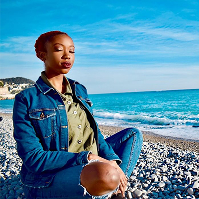 A woman in a denim outfit sitting cross-legged with her eyes close on the beach in Nice, France