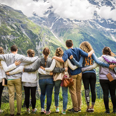 Large group of students hugging against mountain background